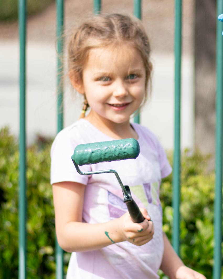 Little girl serving her city by painting a faded fence.